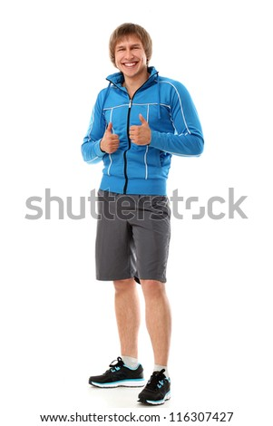 Cute and attractive sport guy smiling and showing thumbs up isolated on a white