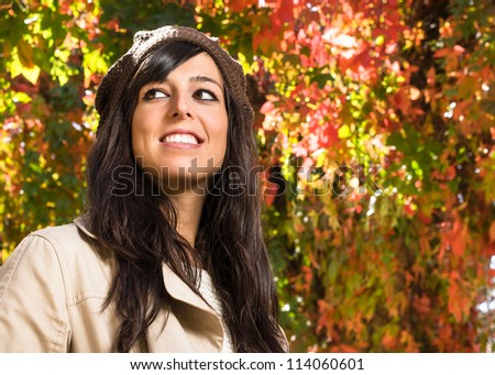 Cute and beautiful young brunette woman smiling in autumn on colorful leaves background