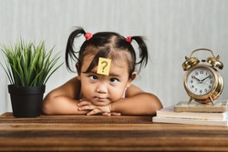 cute and confused lookian asian toddler with question mark on her forehead. concept of child learning education, growth and development.
