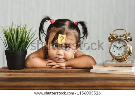 Photo of  cute and confused lookian asian toddler with question mark on her forehead. concept of child learning education, growth and development.