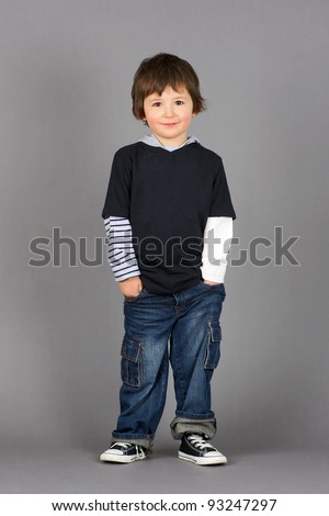 Cute and hip little preschooler boy with big brown eyes smiling with hands in his jeans pockets over grey background.