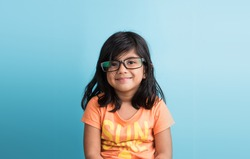 Cute and Joyful little Indian girl posing in front of camera , against sky blue background