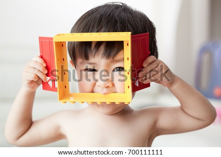 cute and naked baby boy smile with hold toy block, baby has playful expression on his face