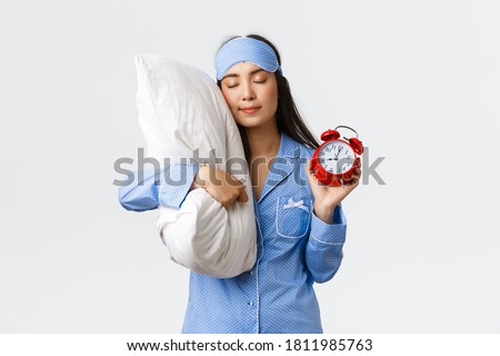 Cute and silly asian girl in blue pyjamas and sleeping mask, sleeping on pillow with closed eyes and showing alarm clock, having sweet dreams as forgot set up alarm, white background Stock photo ©