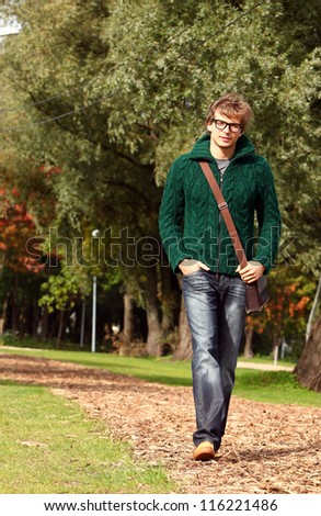 Cute and smart guy walking at cold autumn day in sunny park