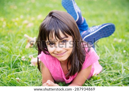 Cute and sweet girl lying in the grass smiling