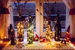 Cute and warm Christmas decoration set with vintage beer bottles and wine bottles filled with micro led party lights, behind the window is countryside forest. Bottles vases for red artificial berry.