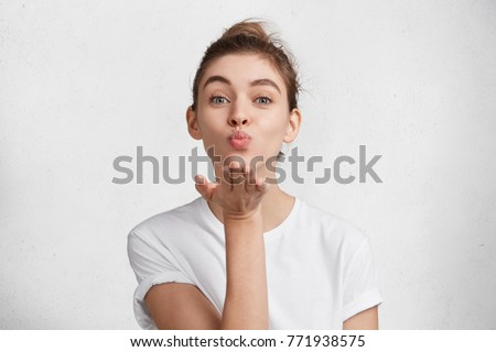 Cute appealing female blows kiss at camera, demonstrates love to boyfriend or says goodbye on distance, isolated over white studio background. Attractive young woman shows sympathy to someone #771938575