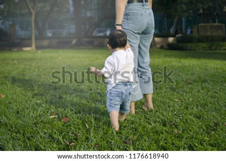 Cute Asian baby boy in white shirt and denim jeans taking his first steps barefoot on fresh grass at the park while holding his mother's hand.
