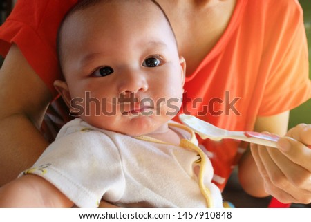 Cute Asian baby boy newborn eating glutton by mother feeding food supplements for babies, Child bored with food.