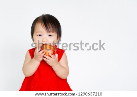 15d74739ff9 Cute asian baby girl bite an red apple and wear the red chinese newyear  dress on
