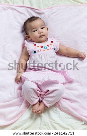 Cute Asian baby girl lay down on blanket sheet