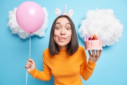 Cute Asian birthday girl looks with temptation at camera licks lips wants to eat delicious cake has special occasion celebrates 26th bday holds inflated balloon enjoys festive party poses indoor