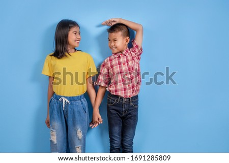 Cute Asian boy and girl measuring their height on sky blue background Foto stock ©