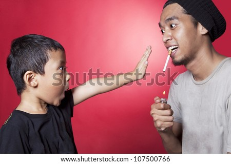 Cute asian boy asking a smoker to stop smoking. shot in studio over red background