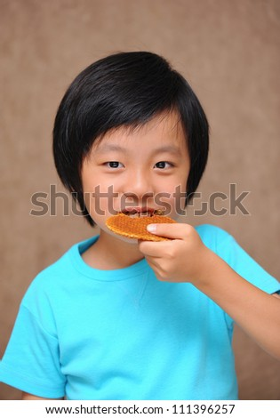 Cute Asian boy enjoying a cookie
