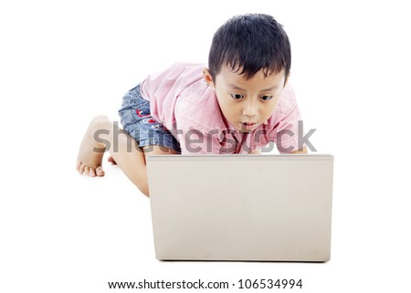 Cute asian boy using laptop computer seriously. shot in studio