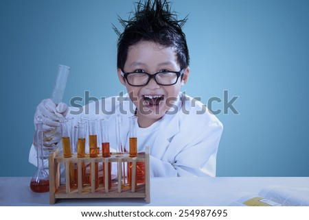 Cute asian boy wearing lab coat doing experiment like a mad scientist