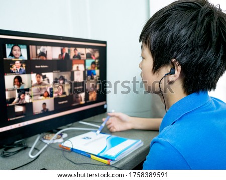 cute asian boy with earphone, sitting at desk ,using pc for having video conference chat with teacher and class group at home. Study Online remote learning, Homeschooling during coronavirus outbreak.
