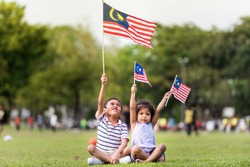Cute Asian Brother and Sister/Siblings waving the Malaysia Flag, sitting down on the grass. Merdeka Celebration.