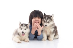 Cute asian child and siberian husky puppies lying on whitebackground,isolated