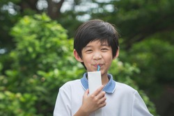 Cute Asian child  drinking a carton of milk from a box with a straw