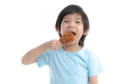 Cute Asian child eating fried chicken on white background isolated
