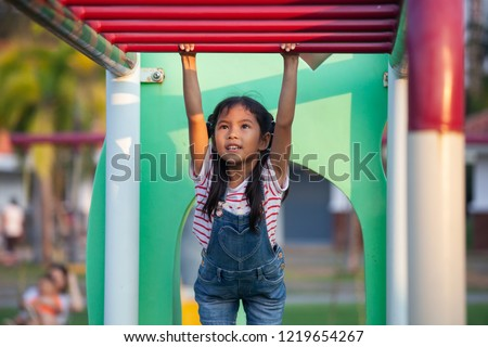 Cute asian child girl hang the bar by her hand to exercise in the playground