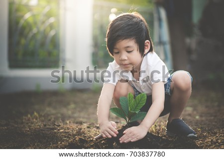 Cute Asian child planting young tree on the black soil #703837780