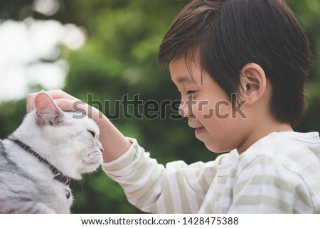 Cute Asian child playing with british cat in the park outdoor