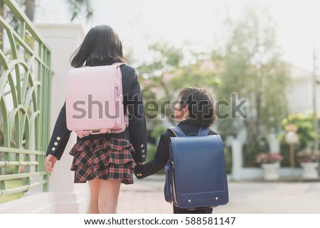 Cute Asian children  holding hand  together while  going to the school outdoors,back to school concept