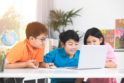 Cute Asian children using laptop together with smile face.