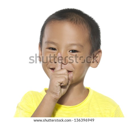 Cute asian elementary school student with his finger over her mouth, hushing.