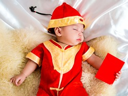 cute asian four-month baby in chinese traditional red dress sleeping with red envelope of money gift  in chinese newyear festival. Happy chinese new year concept.
