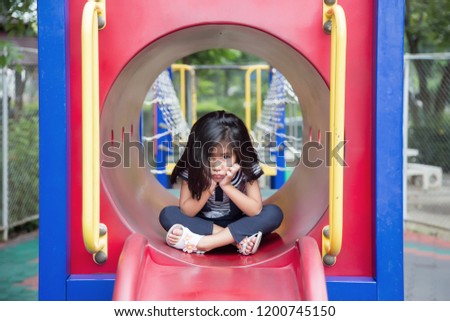 cute asian girl boring play alone in play park outdoor park in summer #1200745150