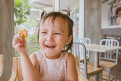 Cute asian girl eating Chicken Nugget by self. Background. Copy space.