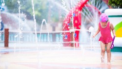 Cute Asian girl is joyfully stepping on fountain rising from ground. Kid in red swimming suit is playing in water in summer. Happy childhood. Fountain in water park located in city. Child 3-4 year old