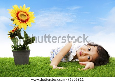 Cute asian girl laying on the grass shot with sunflower in spring - stock photo