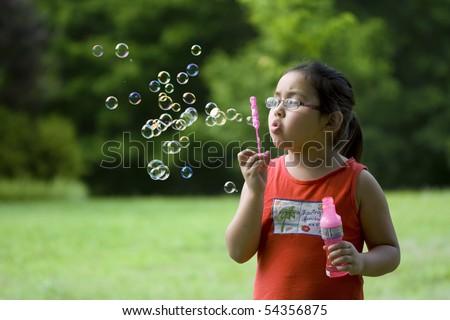Cute Asian girl outside blowing bubbles