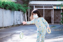 Cute Asian girl playing throw a ring. Child wear mask in public areas. Prevent the spread of coronavirus and air pollution PM2.5. Children do morning exercises after waking up. Kid is in green pajamas