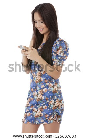 Cute Asian girl smiling while using her cellphone over a white background