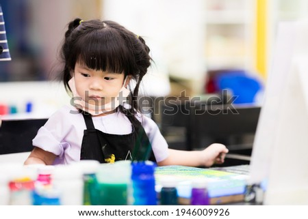 Cute Asian girl studying art. Children are in watercolor crafts class. Child take a cloth mask under their chin. Kids wears a black apron. Baby aged 3-4 years old. Stock photo ©