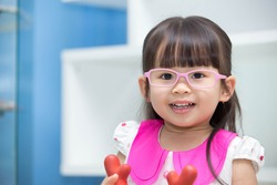 Cute Asian girl wearing glasses. playing toys happily.