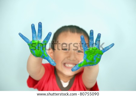 Cute asian kid showing his hands painted in blue and green
