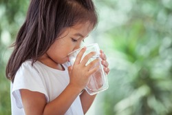 Cute asian little child girl drinking fresh water from glass on green nature background