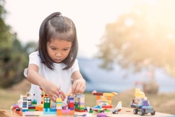 Cute asian little child girl playing with colorful blocks. She is creating and building her toy with fun in good weather outside.