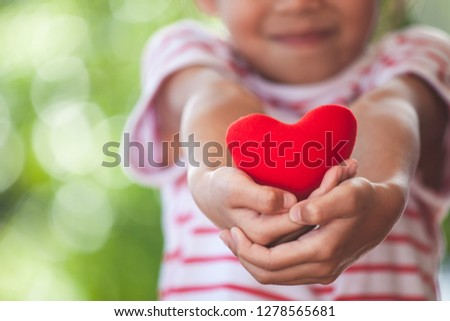 Cute asian little child girl showing and holding red heart in hand with care and love #1278565681