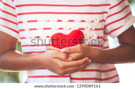 Cute asian little child girl showing and holding red heart in hand with care and love #1290089161
