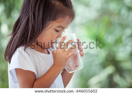 Cute asian little girl drinking fresh water from glass on green nature background