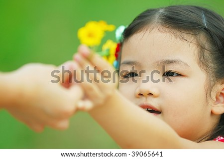 Cute Asian little girl gives flower to her mother - stock photo